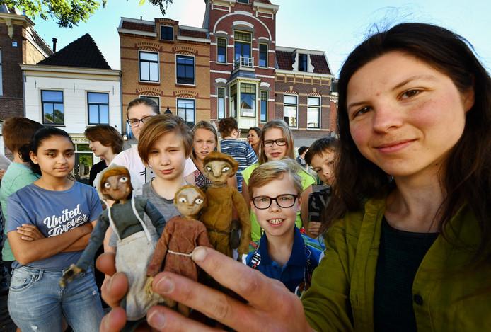 Scholieren bekijken de poppen die Roos Mattaar heeft gemaakt voor haar animatiefilmpje.