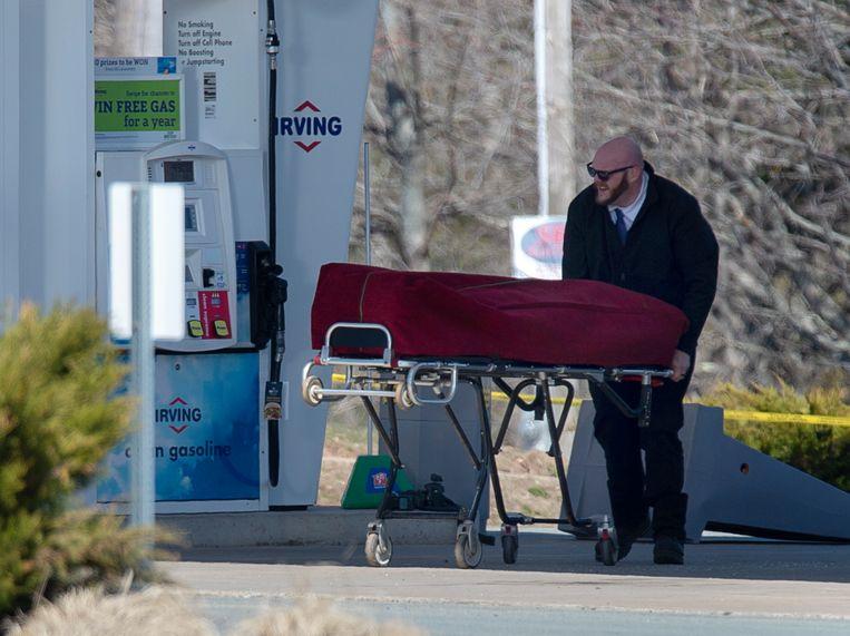 Een van de lichamen wordt zondagochtend afgevoerd nadat een als politieagent verklede man zeker zestien mensen doodschoot in Nova Scotia, Canada. Beeld AP