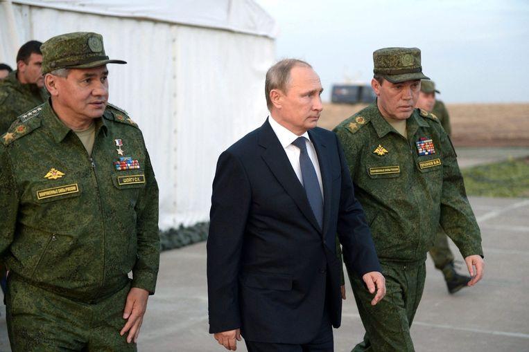 Vladimir Poetin, de leider van Rusland, met een minister en stafchef van het leger.  Beeld afp