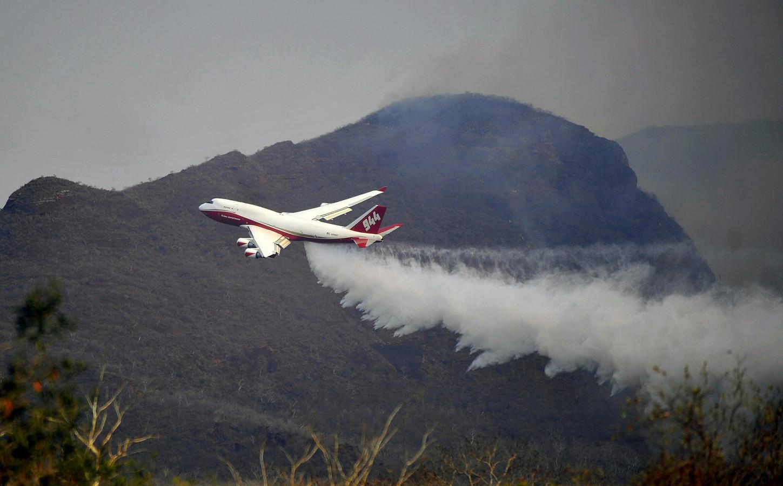 Het Boeing SuperTanker blusvliegtuig stort bluswater uit boven het brandende bosgebied bij Robore in de oostelijke Boliviaanse regio Santa Cruz.