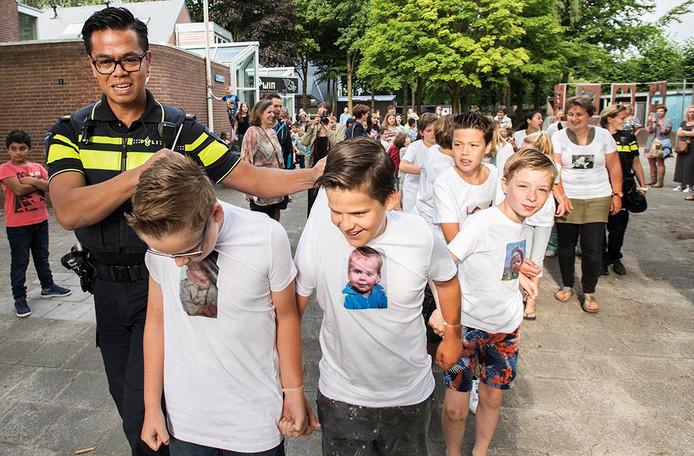 Wijkagent Ed Kain arresteert schooklas groep 8 van bs Darwin in Oisterwijk.