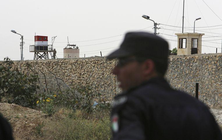 Op de achtergrond Egyptische militairen aan de grenspost in Rafah, op de voorgrond een Hamas-veiligheidsagent.