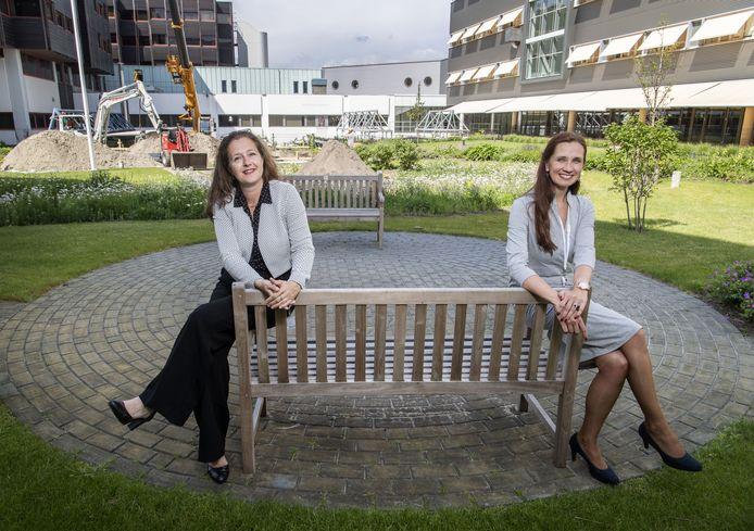 Bestuursvoorzitter Sophia de Rooy (links) en fondsenwerver Rianne Ligtenberg  van het MST in de binnentuin. Op de achtergrond wordt gebouwd aan het paviljoen voor IC-patiënten.