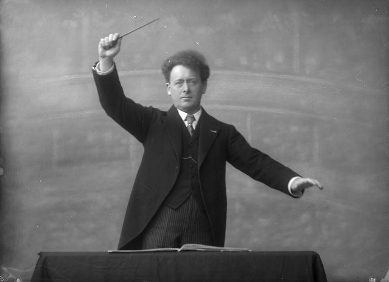 Portret van dirigent Willem Mengelberg (1871-1951). In de studio geportretteerd alsof hij op de bok staande dirigeert, met als achtergrond de grote zaal van het Concertgebouw ingetekend. Beeld Beeldbank Stadsarchief Amsterdam