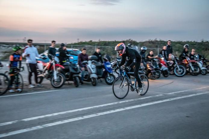 Sprinten op een racefiets, met helm op.