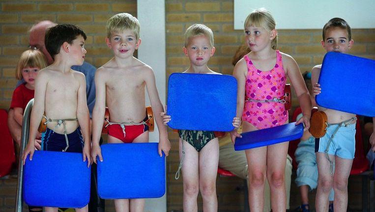 Kinderen wachten op de rand van het bad tot ze het water in mogen springen. Beeld anp
