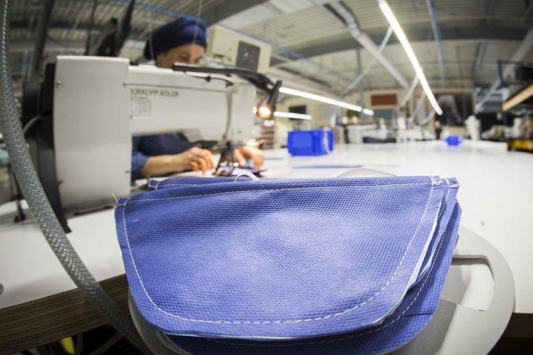 Medewerkers bereiden mondkapjes voor in een naaiatelier van beddenfabrikant Auping. Beeld ANP