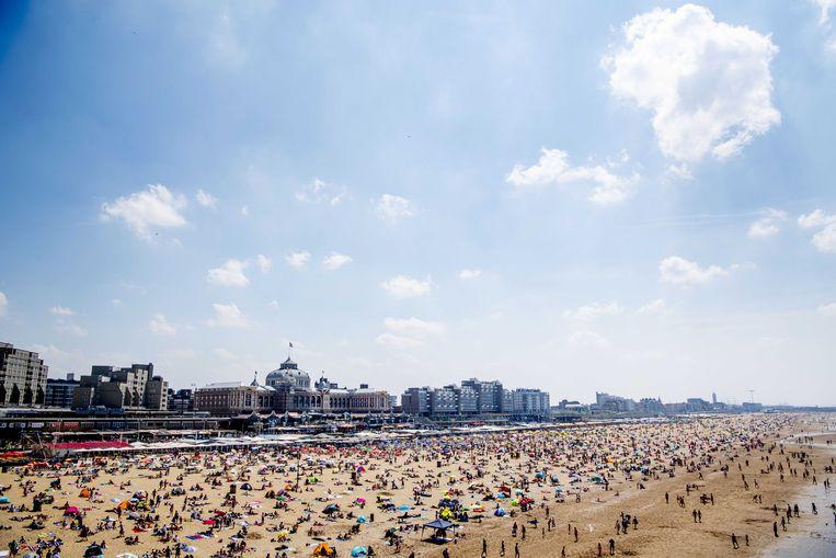Een vol strand in Scheveningen (Den Haag), een van de bekendste en grootste badplaatsen van Nederland. Op de dijk staat het imposante Kurhaus.