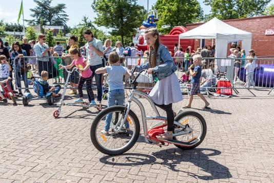 Celia doet tijdens de buitenspeeldag in Kapelle een stukje op een fiets met wel héél grote trappers.