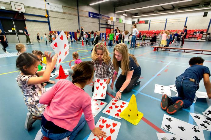 Zo'n 200 leerlingen van groep 3 en 4 uit de Bossche wijk de Maaspoort doen spelletjes uit de nieuw ontwikkelde Rekenbeweegbox. In het midden studente Jenneke Kradolfer die een coördinerende rol speelt bij dit project.