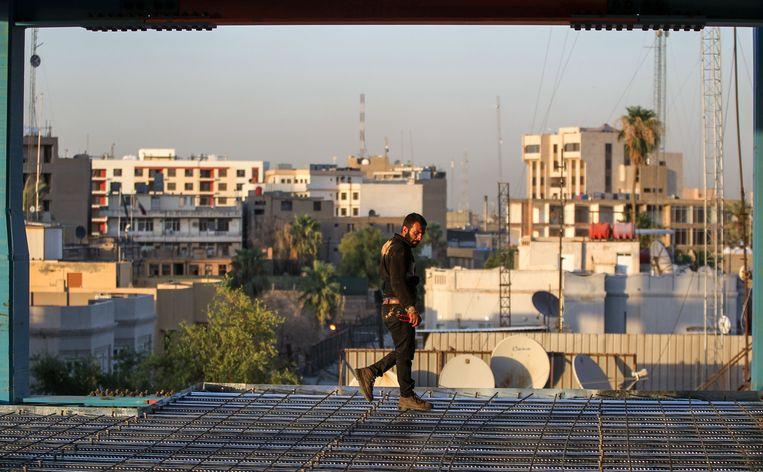 Een bouwvakker loopt over een bankkantoor in aanbouw in de Iraakse hoofdstad Bagdad. Beeld AFP