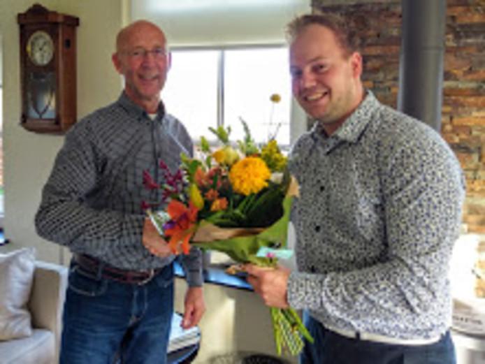 Thom de Vries (rechts) uit Kalenberg reikt een bloemetje uit in Ossenzijl aan Piet Mur. Alweer de 50e klant op de lijst.