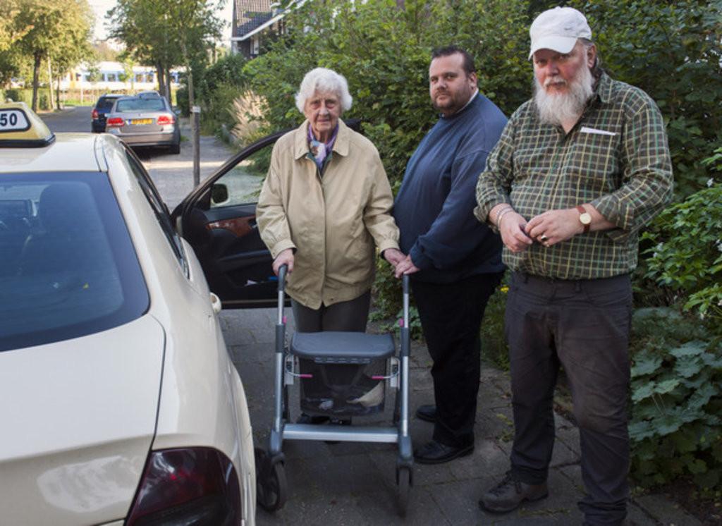 Taxichauffeur Vincent Leek (midden) en de vrouw met haar zoon die hij regelmatig ophaalt.