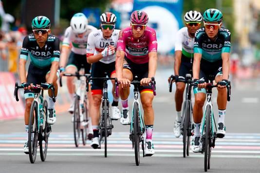 De gehavende Pascal Ackermann komt omringd door ploegmaten over de finish.