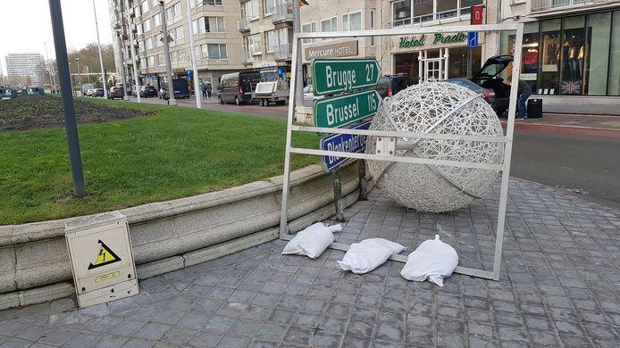 Deze enorme kerstbal wordt in Oostende op zijn plaats gehouden door zandzakjes.