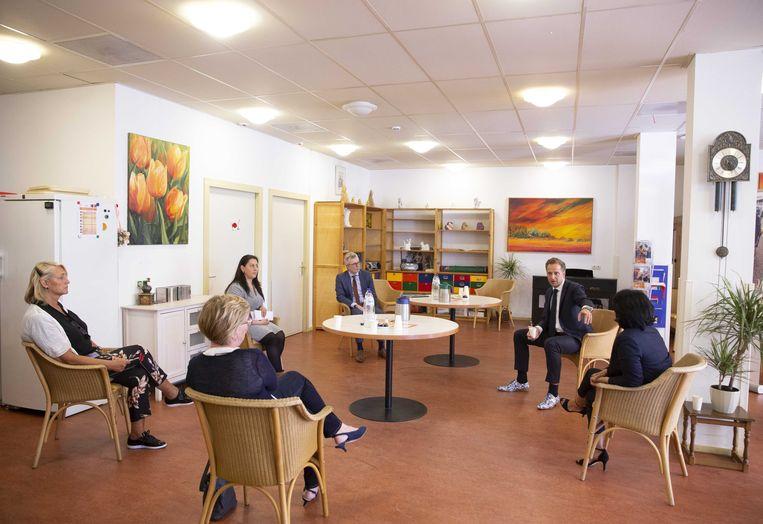 Minister Hugo de Jonge van volksgezondheid praat met medewerkers van Humanitas-locatie De Zilverlinde in Rotterdam. Beeld ANP
