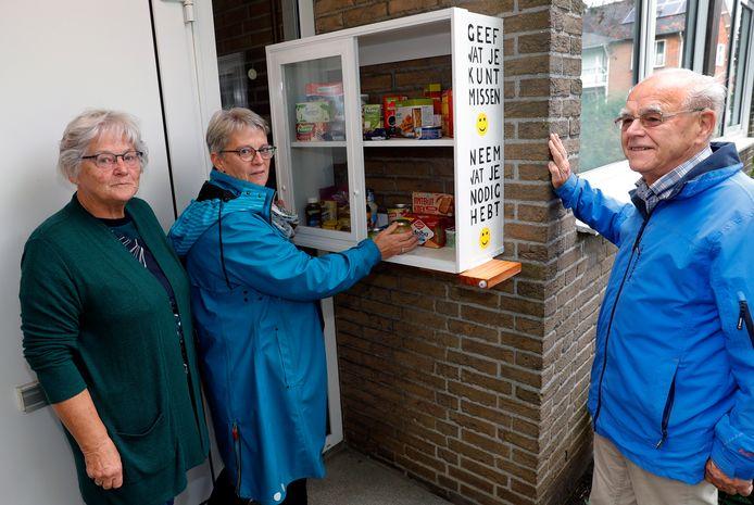 Betty Haveman en Henny van Onselen met Martinus Roorda bij de voedselkast.
