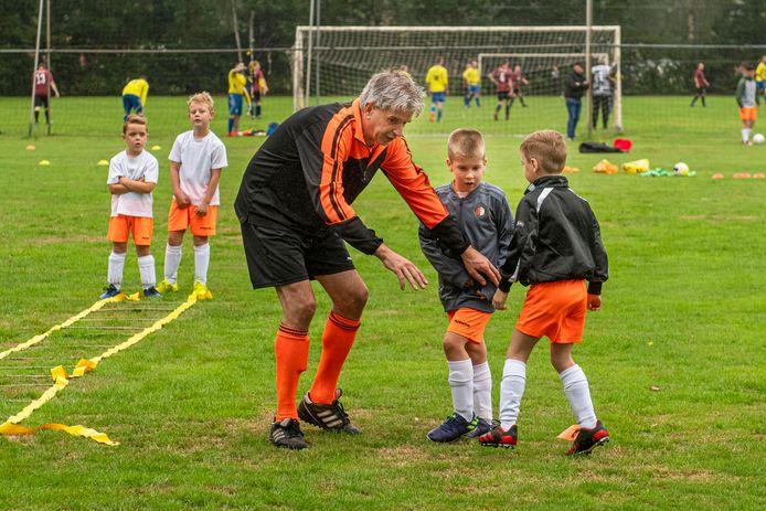 Mark van de Sande geeft uitleg aan twee kinderen tijdens de training van Voetbal Academie Brabant.