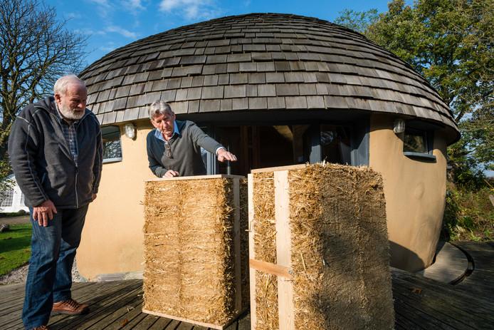 Pim Hondeveld (r)  laat bezoeker Wim Kloosters (l) details zien van het  strohuis gebouwd met door Hondeveld ontwikkelde Straw blocks systems.
