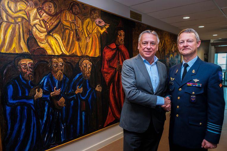 Kolonel Briers van CRC Glons en burgemeester Patrick Dewael geven elkaar de hand als teken van hernieuwde samenwerking en vriendschap. Om die band toonbaar te maken, schonk de kolonel een schilderij aan de stad.