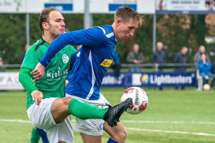 Lennart Rekmans van RKHVV beschermt de bal tegen zijn tegenstander van Heino.