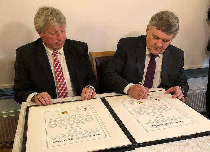 Burgemeesters Henk Lambooij (r) en Lutz Martensen ondertekenen de stedenband tussen Putten en Ladelund.