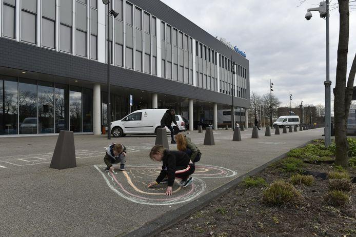 Milo, Fenna, Brechje en hun vader Mark druk aan het stoepkrijten voor het Catharina Ziekenhuis in Eindhoven.